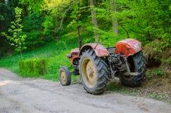 在乡下公路的老拖拉机 免版税库存照片