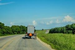 在乡下公路的门诺派中的严紧派的儿童车在威斯康辛 免版税图库摄影