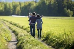 在乡下公路的年轻家庭 免版税库存照片