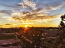 在乡下在培养的领域上和太阳的令人惊讶的日落在树之间传播它的光芒 免版税图库摄影