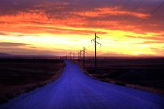 在乡下日落或日出的电话电源杆 免版税库存照片