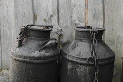 在乡下染黑并且上油了金属罐 木的墙壁 免版税库存照片