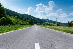 在乡下,路旁的,充满活力的天空蔚蓝森林柏油路 免版税库存图片