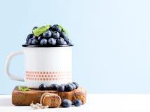 在乡村模式的搪瓷的新鲜的成熟蓝莓在蓝色淡色背景的土气木板抢劫 库存图片
