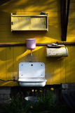 在乡间别墅的黄色墙壁上的桃红色水盆 免版税库存图片