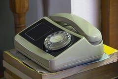 在书上把放的老白色电话 免版税库存图片