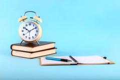 在书和开放笔记本的老时钟在蓝色背景 库存照片