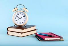 在书和笔记本的老时钟有在蓝色背景的笔的 库存图片