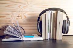 在书和飞行笔记的耳机 audiobooks的概念 免版税库存照片