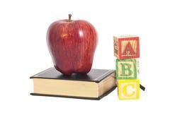 在书和ABC木信件块的红色苹果 免版税库存照片