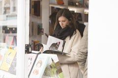 读在书店的逗人喜爱的妇女新书 库存照片