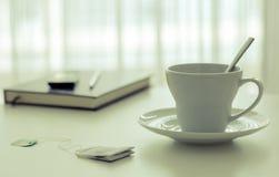 在书旁边的在窗口附近的茶杯和笔 免版税库存照片