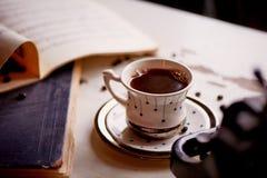 在书旁边的舒适咖啡杯 在温暖的口气的减速火箭的摄影  图库摄影