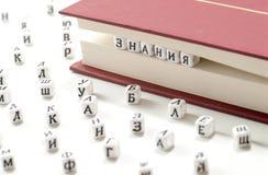 在书板料和斯拉夫语字母的信件之间的词知识书面胜利斯拉夫语字母的信在白色背景概念摘要驱散 免版税库存照片