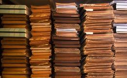 在书架、书架背景、堆旧书和纸的老古色古香的书 库存照片