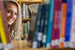 在书架中的微笑的女性在大学图书馆里 免版税库存照片