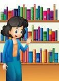 在书架前面的一位图书管理员有书的 免版税库存照片