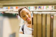在书架后的大学生 库存照片