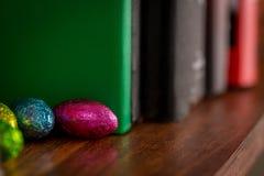 在书架掩藏的复活节巧克力 库存图片