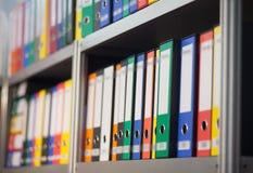 在书架的五颜六色的文件夹 免版税库存照片