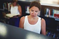 在书架的年轻亚洲女性搜寻的书 免版税图库摄影