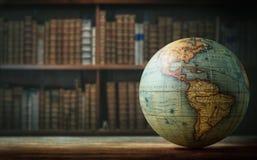 在书架背景的老地球 选择聚焦 减速火箭的样式 免版税图库摄影