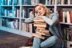 在书架附近的白女孩在图书馆里 学生与在她的膝部的书睡觉 库存图片