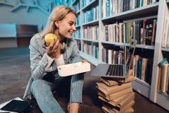 在书架附近的白女孩在图书馆里 学生吃着从饭盒的苹果 库存图片