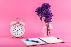 在书桌、笔记本和开放花上的老时钟在桃红色背景的一个花瓶 免版税图库摄影