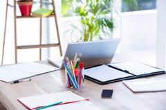 在书桌上的一台便携式计算机 免版税库存图片