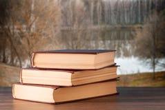 在书桌上的三本书反对背景 免版税库存照片