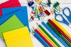 在书桌上的五颜六色的学校必需品 图库摄影