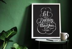 在书桌上的刺激印刷术印刷品对绿色墙壁 免版税图库摄影