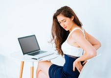 在书桌上的年轻白种人工作的女商人有遭受更加低后和熟悉内情的痛苦的膝上型计算机的结果办公室综合症状 免版税库存照片