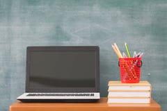 在书桌上的教科书,回到学校用品 书和黑板在木背景,教育概念 图库摄影
