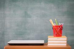 在书桌上的教科书,学校用品 书和黑板背景,网上教育,教育概念 免版税库存图片