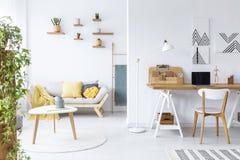 在书桌上的海报有在白色客厅内部的膝上型计算机的与长沙发和木桌 实际照片 免版税库存图片