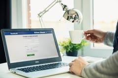 在书桌上的现代膝上型计算机在有Facebook网站的办公室在屏幕上 免版税库存照片