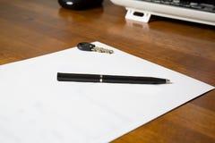 在书桌上的白纸有笔和钥匙的 免版税库存图片
