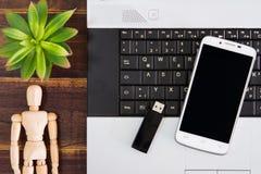 在书桌上的笔记本计算机, USB闪光推进棍子,智能手机 库存图片