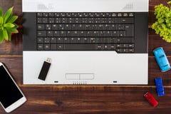 在书桌上的笔记本计算机, USB闪光推进棍子,智能手机 免版税库存图片