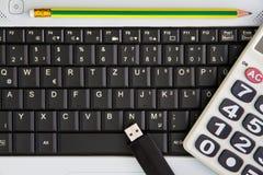 在书桌上的笔记本计算机 计算器, USB闪光推进棍子, 免版税库存图片