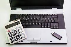 在书桌上的笔记本计算机 计算器, USB闪光推进棍子 免版税库存照片