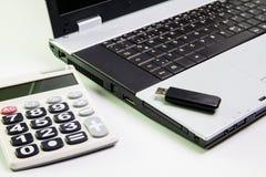 在书桌上的笔记本计算机 计算器, USB闪光推进棍子 库存图片