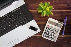 在书桌上的笔记本计算机 计算器, USB闪光推进棍子 免版税库存图片
