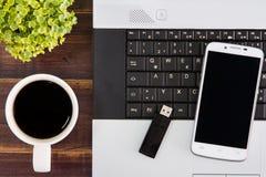 在书桌上的笔记本计算机 USB闪光推进棍子,咖啡杯, s 库存照片