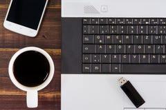 在书桌上的笔记本计算机 USB闪光推进棍子,咖啡杯, s 免版税库存图片