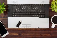 在书桌上的笔记本计算机 USB闪光推进棍子,咖啡杯, s 免版税库存照片