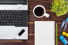在书桌上的笔记本计算机 USB闪光推进棍子,纸,咖啡 免版税库存照片