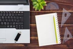 在书桌上的笔记本计算机 USB闪光推进棍子,纸 库存图片